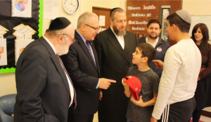 Dr. Joshua Weinstein (left), Assemblyman Steven Cymbrowitz (middle), Mr. Ezra Friedlander (right) greeting students at SKHOV