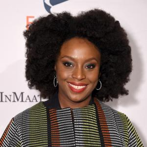 Chimamanda Ngozi Adichie smiling to camera against wall with Equality Now logos