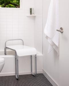 The Judith Bench helps keep caregivers and loved ones safe by providing assistance when needed. This image shows the Judith bench with a solid frost seat and adjustable chrome frame. The bench is positioned in a bathtub for bath or shower use.
