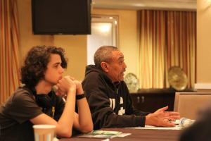 A member of Washington, DC's, vibrant Ethiopian community explains rights issues, as a youth participant listens.