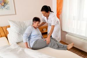 caregiver helping elderly client to bed