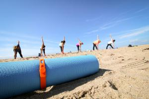 Packbands securing rolled yoga mat on the beach
