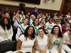 ERA Congressional Hearing, May 2019 - sitting left to right, Jennifer Carroll Foy, Alyssa Milano, Kate Kelly; a group of women sit behind them; everyone is wearing white, many are smiling