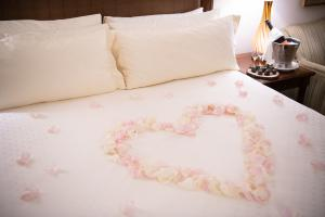 Heart-shaped rose petals on the bed
