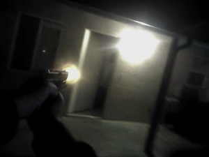 After dodging the tossed yearbook, Modesto Police officer Dave Wallace, in this screen grab, fires his service weapon at Jesse Montelongo, who is retreating into his house.