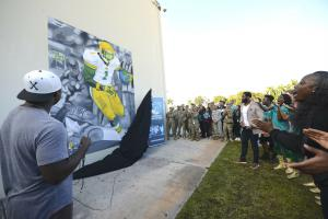 Artist Ju Reams (left) unveils the mural he created at the high school where former NFL safety Nick Ferguson (center) went to school and got his start in football.