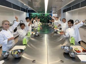 Students cooking in chef coats in Little Kitchen Academy