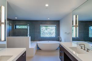 A beautiful master bathroom with pedestal soaking tub walk in shower and dual vanities