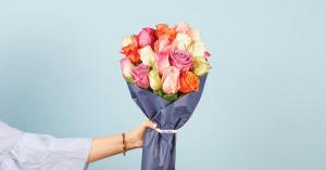 Handing bouquet of multi-color roses on blue backdrop.