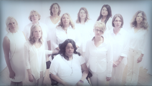 Survivors of intimate partner homicide attempts whose stories were featured in the documentary film, Finding Jenn's Voice, gather as a group dressed in white looking to camera