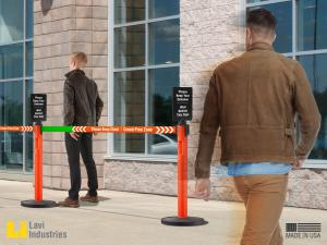 Customers keeping a safe social distance while queuing with the help of printed signage and retractable belt stanchions