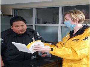 Sharing How to Keep Yourself & Others Well  booklet with a security guard at a local hospital.
