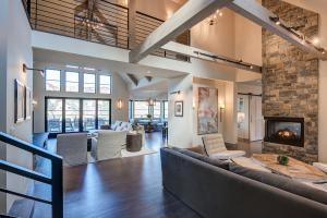 Great room with high beamed vaulted ceiling stone fireplaces and windows overlooking Lake Sonoma