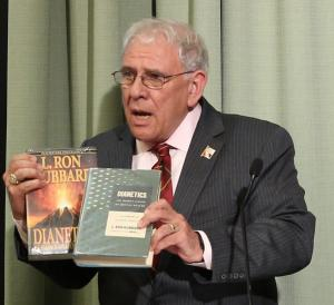 Chairman and historian of the L. Ron Hubbard Foundation Mr. Bill Runyon holds up an original copy of Dianetics: The Modern Science of Mental Health from 1950, along with the more familiar – and more colorful -  current edition.