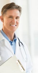 Male doctor holding clipboard smiling