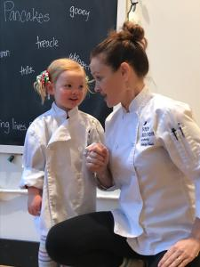 Founder of LKA kneeling down wearing chef coat next to young girl student in chef coat