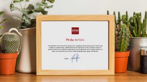 A physical framed Giving What We Can Pledge certificate on a shelf