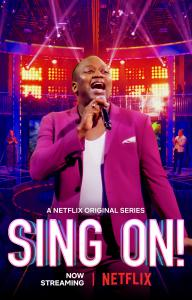 TV Host Tituss Burgess stands on stage with the Sing On Logo!