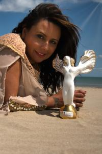 "Viviana Puello holding the ATIM Top 60 Masters Official Award, a sculpture created by her entitled ""Rising Above""."