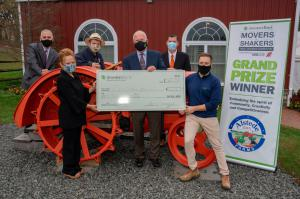 Photo of check presentation, six people stand by an old orange tractor. Three people in front row are holding a large check.