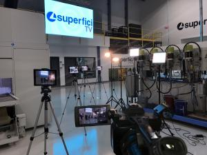 Photograph shows interior of Superfici America's technology center featuring the lights and production cameras for Superfici TV.