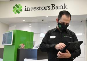 A banker holds a tablet computer and uses a stylus to enter data into the unit.