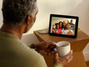 Black senior citizen watches screen as he video chats with family.