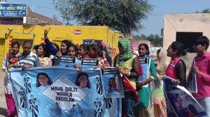 A group of women holding a blue banner, protest on the street to call for greater rights and protections for Dalit women and girls; it is daytime and the sky in the background is blue