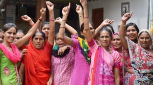 A group of around eleven Indian women wearing saris, looking to camera, many have their arm raised and their mouths open to speak.