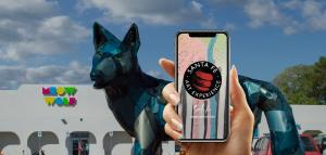 hand holding smartphone phone in front of old bowling alley with a giant dog in front