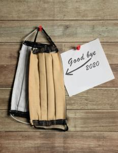 Two face masks hung on a drawing pin with a note reading 'goodbye 2020'