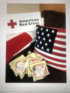 KN95 masks in packaging surrounded by the American Red Cross logo and pillow of the American flag.