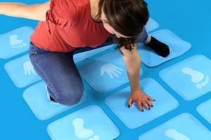 Woman playing hands and feet hopscotch