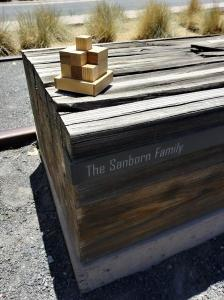 The Sanborn Family bench in Railyard Park, Santa Fe. The tiny angel wings charm was hidden in a crevasse at the end of the bench.