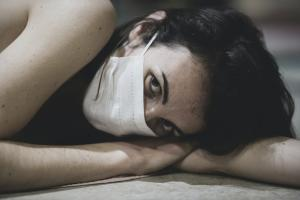 woman alone laying down in mask feeling social isolation due to COVID-19 lockdowns
