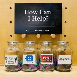How Can I Help by Little Kitchen Academy sign on chalkboard with 4 glass jars and logos of Chefs for Humanity, PHIT America, Global FoodBanking Network, Kids Help Phone