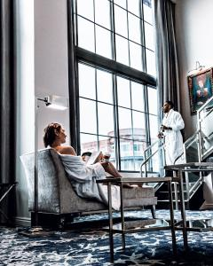 Chris and Reg are both enjoying morning coffee in a beautiful loft style hotel suite that that has 20feet tall floor to ceiling windows. Chris is sitting in a chaise lounge wearing a white robe off off the right shoulder.  Reg is also wearing a white rob
