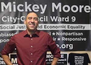Candidate Mickey Moore standing in front of campaign banners