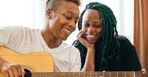 African-American woman playing guitar to her female lovers as they chilling at home.