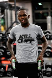 Israel Adesanya in a Kill Cliff shirt with Kill cliff beverage cans in a gym