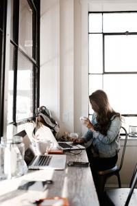woman holding coffee, working on a laptop at desk in well lit room