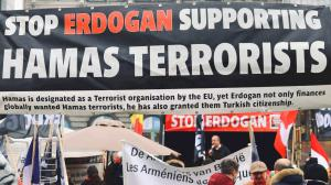 A group of protestors holding a large banner explaining that Erdogan supports Hamas, a terrorist organisation.