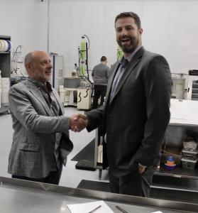 Mark and Joe shaking hands in a factory