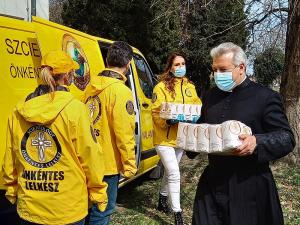 Catholic priest helps unload supplies donated by the Scientology Volunteer Ministers for needy families in his diocese.
