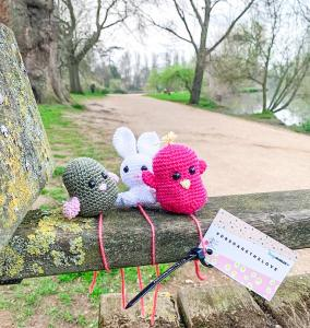 Three handmade knitted animals on a riverside bench in Oxford