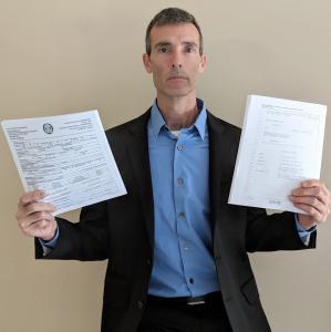 SubscriberWise founder and America's child identity guardian David Howe, holding two public records each containing sworn testimony which has been provided to USA Congress, law enforcement, and media confirming profound consumer UDAAPs.