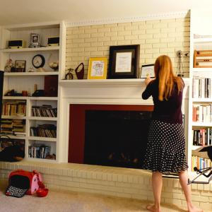 woman adjusting Smile Songs art prints that sing on fireplace mantel