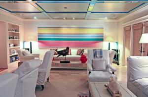 A photo of a Florida-style living room decorated with a large abstract painting by Kenneth Noland, comfortable furniture, photos and decorative objects.