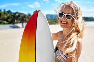 Smiling girl at beach holding surfboard