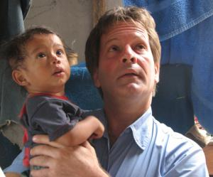 Author and human rights activist Patrick Atkinson rescues a small Guatemalan boy from village affected by Mount Fuego volcanic eruption
